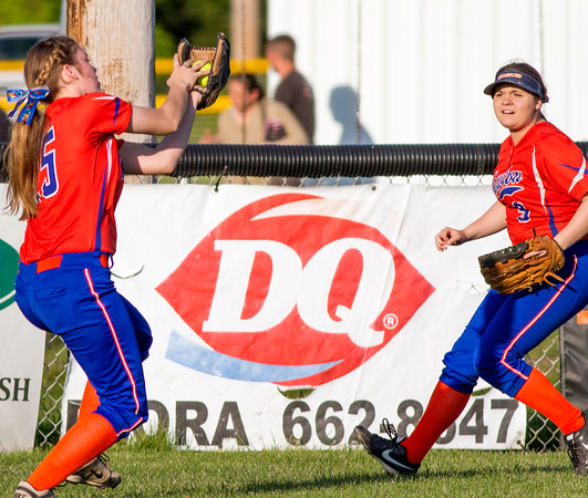Newton center fielder Kaitlyn Cohorst makes a grab while right fielder Julia Earnest comes in for support at the Class 2A Flora Regional.