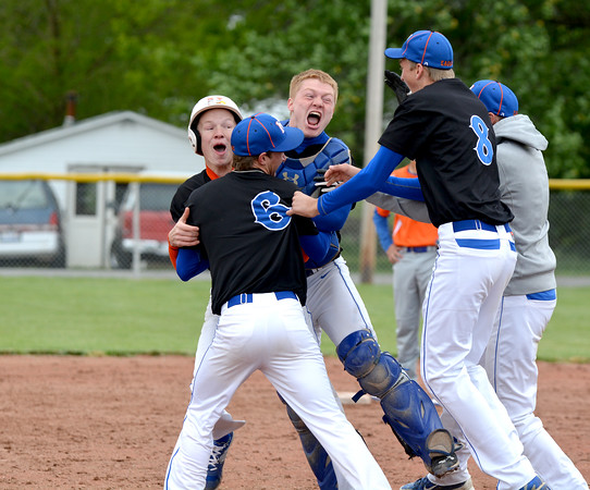 Newton's John Grunloh (left, helmet) and Mitch Bierman (right) are hugged by teammate Tim Weber (6, center) as a group of Newton players approach them following Grunloh's walkoff double to lead Newton past Flora 4-3 in eight innings. Newton clinched the Little Illini Conference championship with the win.