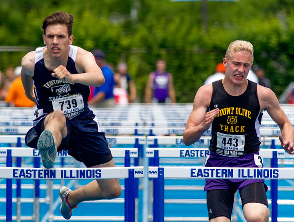 Teutopolis' Noah Blievernicht (left) clears a hurdle next to Mt. Olive's Ethan Swenson during the 110-meter high hurdles at the Class 1A state track preliminary meet. Blievernicht finished fourth in the heat with a time of 16.00.