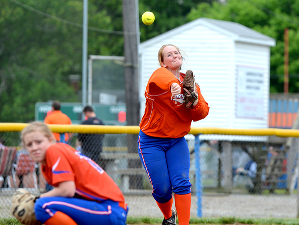 Newton third baseman Maddie Stanley throws the ball to first over a crouched Olivia Shipman (left) during Newton's 7-5 win over Edwards County.