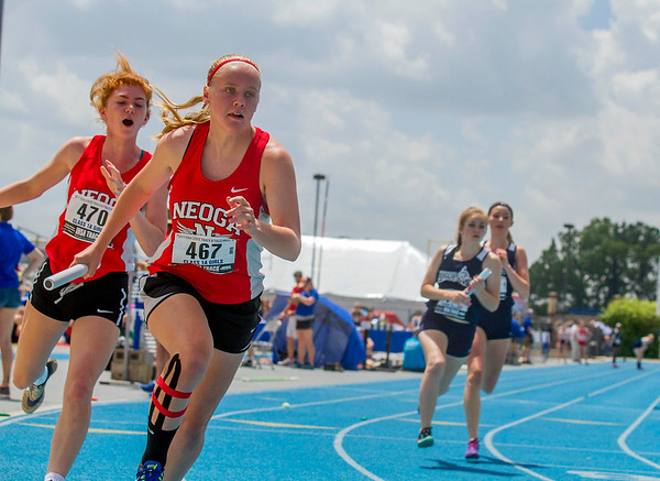 Neoga's Zoe Meadows, left, trails teammate Makenzie Hill after their handoff during the 4x100-meter relay at the IHSA Class 1A State Track Meet Preliminaries in Charleston.