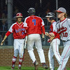 St. Anthony's Joe Kabbes, left, greets Drew Gibson (7) after coming home on Greg Utz' two-run single in the top of the seventh. Effingham's Mason Hull, right, walks back to the mound after covering home. The Flaming Hearts lost a 2-1 lead in the top the of the seventh as the Bulldogs scored four runs to win 5-2 and avoid a sweep in the 36th Annual City Series.