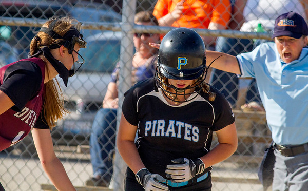 Dieterich pitcher Jennifer Robards, left, looks to the home-plate umpire who calls Cumberland's  Danae Sowers safe during a regional semifinal in Toledo. The Pirates defeated the Maroons 17-0 in four innings to advance to the championship against Neoga.