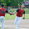 Neoga's Caleb Hill is congratulated at third base by coach Zach Miller (16) after hitting a home run against Cowden-Herrick/Beecher City in regional quarterfinal play at Neoga. It was one of three home runs by Neoga on the day.