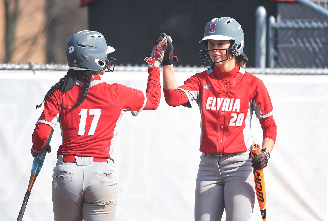KRISTIN BAUER | GAZETTE Elyria High School's Emily Hyer (20) high-fives teammate Dierra Hammons (17) after Hammons scored the first run against Medina on Wednesday afternoon, April 12.
