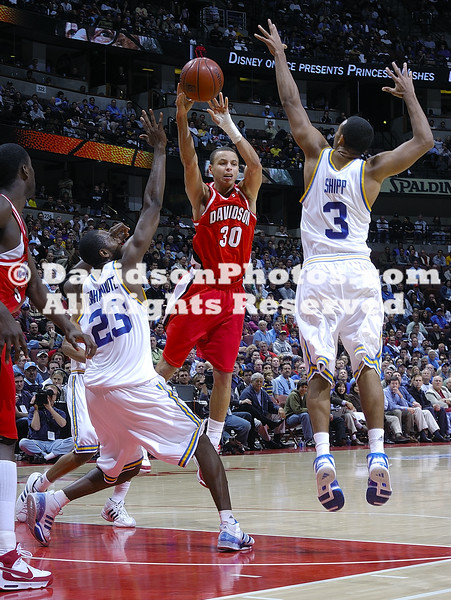 Davidson's Stephen Curry passes under pressure by UCLA