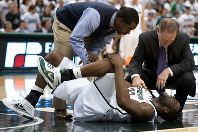 Dec 4, 2011; East Lansing, MI, USA; Michigan State Spartans forward Draymond Green (bottom) is looked over by a trainer and head coach Tom Izzo (right) after hurting his knee in the first half against the Nebraska-Omaha Mavericks at the Breslin Center. Mandatory Credit: Tim Fuller