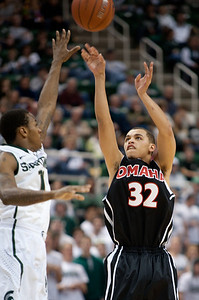 Dec 4, 2011; East Lansing, MI, USA; Nebraska-Omaha Mavericks guard Mitchell Farr (32) gets a shot off over the Michigan State Spartans defender  at the Breslin Center. Mandatory Credit: Tim Fuller