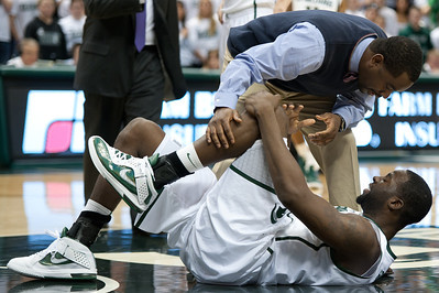 Dec 4, 2011; East Lansing, MI, USA; Michigan State Spartans forward Draymond Green (bottom) is looked over by a trainer after hurting his knee in the first half against the Nebraska-Omaha Mavericks at the Breslin Center. Mandatory Credit: Tim Fuller
