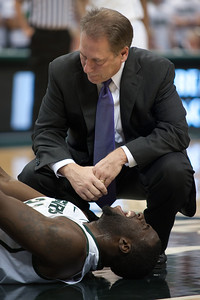 Dec 4, 2011; East Lansing, MI, USA; Michigan State Spartans forward Draymond Green (bottom) is looked over by head coach Tom Izzo (top) after hurting his knee in the first half against the Nebraska-Omaha Mavericks at the Breslin Center. Mandatory Credit: Tim Fuller