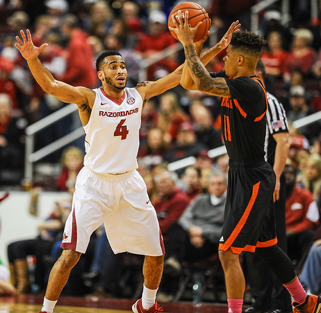 Arkansas Razorbacks guard Jabril Durham (4) defends against Mercer Bears guard Jordan Strawberry (11) during a basketball game between Arkansas and Mercer on December 19, 2015.    (Alan Jamison, Nate Allen Sports Service)
