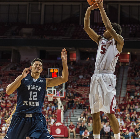 Arkansas Razorbacks guard Anthlon Bell (5) shoots over North Florida Ospreys guard Aaron Bodager (12) during a basketball game between Arkansas and North Florida on December 22, 2015.    (Alan Jamison, Nate Allen Sports Service)