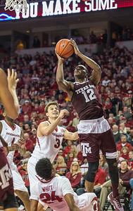 Arkansas Razorbacks guard Jimmy Whitt (24) takes a charge while defending against Texas A&M Aggies guard Jalen Jones (12) during a basketball game between Arkansas Razorbacks and Texas A&M Aggies  on January 27, 2016.    (Alan Jamison, Nate Allen Sports Service)