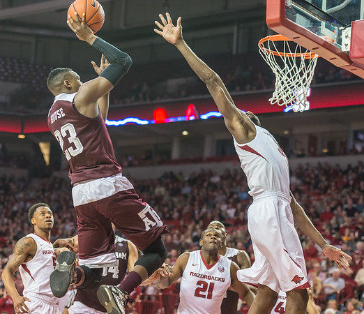 Arkansas Razorbacks forward Moses Kingsley (33) defends against Texas A&M Aggies guard Danuel House (23) during a basketball game between Arkansas Razorbacks and Texas A&M Aggies  on January 27, 2016.    (Alan Jamison, Nate Allen Sports Service)