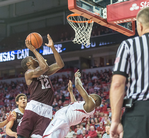 Arkansas Razorbacks forward Moses Kingsley (33) takes a charge while defending Texas A&M Aggies guard Jalen Jones (12) during a basketball game between Arkansas Razorbacks and Texas A&M Aggies  on January 27, 2016.    (Alan Jamison, Nate Allen Sports Service)