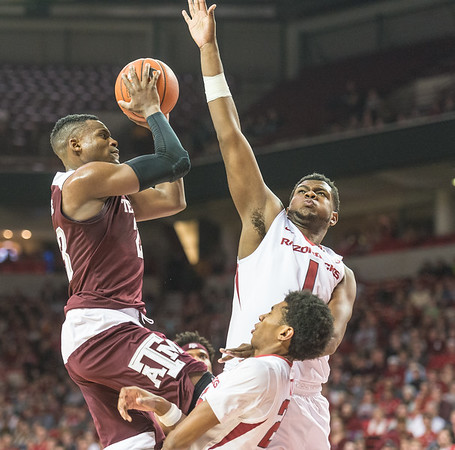 Arkansas Razorbacks guard Jimmy Whitt (24) takes a charge while defending Texas A&M Aggies guard Danuel House (23) while Arkansas Razorbacks forward Trey Thompson (1) swats at the shot during a basketball game between Arkansas Razorbacks and Texas A&M Aggies  on January 27, 2016.    (Alan Jamison, Nate Allen Sports Service)