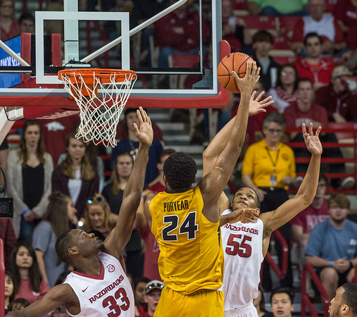 Arkansas Razorbacks forward Moses Kingsley (33) and Keaton Miles defend a shot by Missouri Tigers forward Kevin Puryear (24) during a basketball game between Arkansas and Missouri on 2-20-16.   (Alan Jamison, Nate Allen Sports Service)