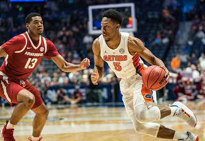 Florida Gators guard KeVaughn Allen (5) drives past Arkansas Razorbacks guard Mason Jones (13) during an SEC Tournament basketball game between the Arkansas Razorbacks and the Florida Gators on Thursday, March 14, 2019, at Bridgestone Arena.  (Alan Jamison, Nate Allen Sports Service)