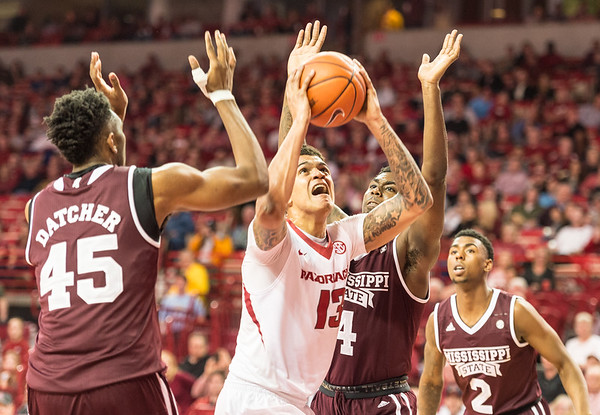 Arkansas Razorbacks forward Dustin Thomas (13) goes up for a shot in a crowd of Mississippi State defenders during a basketball game between Arkansas and Mississippi State on Tuesday, January 10, 2017.  (Alan Jamison, Nate Allen Sports Service)