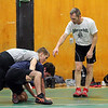 Michael Dube, 15, of Lancaster will be wrestling for Nashoba Regional High School this winter.As he wrestles with alumni Joel Sharin during Monday's practice at the school he gets some instructions from coach George Gilbride. SENTINEL & ENTERPRISE/JOHN lOVE