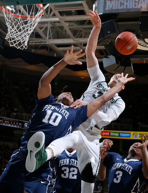 . Penn State\'s Brandon Taylor (10) and Michigan State\'s Gavin Schilling, right, battle for a rebound during the second half of an NCAA college basketball game, Wednesday, Jan. 21, 2015, in East Lansing, Mich. Michigan State won 66-60. (AP Photo/Al Goldis)