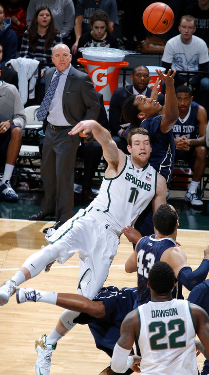 . Michigan State\'s Matt Costello, center, and Penn State\'s Brandon Taylor, rear, leap for a rebound during the first half of an NCAA college basketball game, Wednesday, Jan. 21, 2015, in East Lansing, Mich. (AP Photo/Al Goldis)