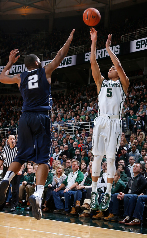. Michigan State\'s Bryn Forbes shoots a 3-pointer against Penn State\'s D.J. Newbill (2) during the second half of an NCAA college basketball game, Wednesday, Jan. 21, 2015, in East Lansing, Mich. Michigan State won 66-60. (AP Photo/Al Goldis)