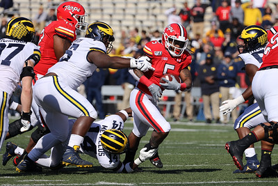 Terps RB Anthony McFarland breaks free of tackles by Michigan defenders.