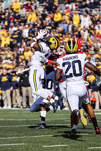 Michigan SS Josh Metellus makes a leaping interception.