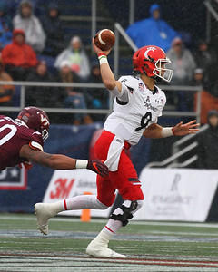 Cincinnati quarterback #9 Desmond Riddler passes the ball under pressure from Virginia Tech defensive end #40 Emmanuel Belmar