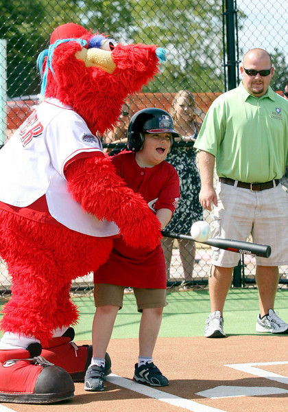 E.L. Hubbard Photography<br /> Zachary Wright, 10, connects for a hit with help from Gapper, the Cincinnati Reds mascot,  during the Miracle League Park Complex of Warren County and Greater Dayton ribbon cutting and opening day at Springboro Junior High School Saturday, September 19, 2009.