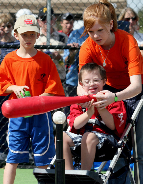 E.L. Hubbard Photography<br /> Isaac Thompson bats as Jake Boulton, 9, and Sammy Oda, 14, offer assistance during the Miracle League Park Complex of Warren County and Greater Dayton ribbon cutting and opening day at Springboro Junior High School Saturday, September 19, 2009.