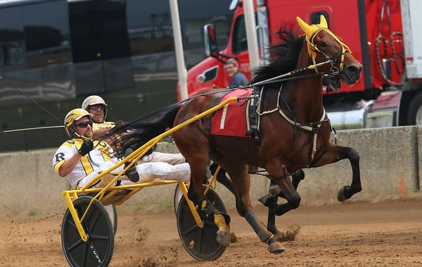 Matt Rheinheimer and Luv Lorelei (1) battle Doug Rideout and Walk With Me in the third race of 11 during Saturday's harness racing action at the Elkhart County 4-H Fair in Goshen.