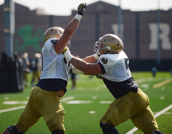 HALEY WARD   THE GOSHEN NEWS<br /> Offensive linemen Trevor Ruhland (left) and Quenton Nelson (right) practice blocking during Notre Dame football practice Wednesday.