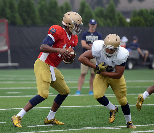 HALEY WARD   THE GOSHEN NEWS<br /> Quarterback DeShone Kizer fakes handing off the ball to running back Josh Anderson while running drills during Notre Dame football practice Saturday.