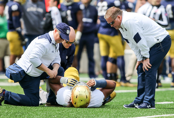 CHAD WEAVER   THE GOSHEN NEWS<br /> Notre Dame trainers attend to freshman offensive lineman Aaron Banks as head coach Brian Kelly looks on during the first half of Saturday's Blue-Gold game at Notre Dame Stadium.