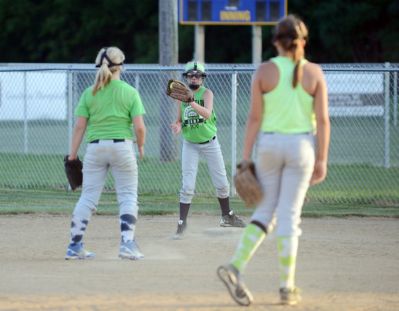 HALEY WARD | THE GOSHEN NEWS <br /> Kenlee Gall catches a ball from Sydney Stutsman (left) as Brooke Sanchez (right) watches listen to their coach following practice on Monday at Hoover Field in New Paris.