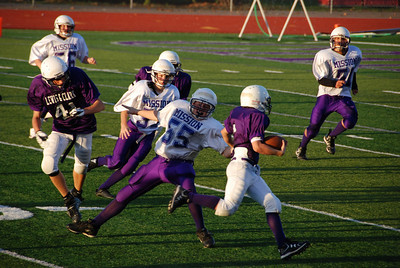 Mission's Austin Anderson no. 55 tries to stop a Lewis & Clark run.