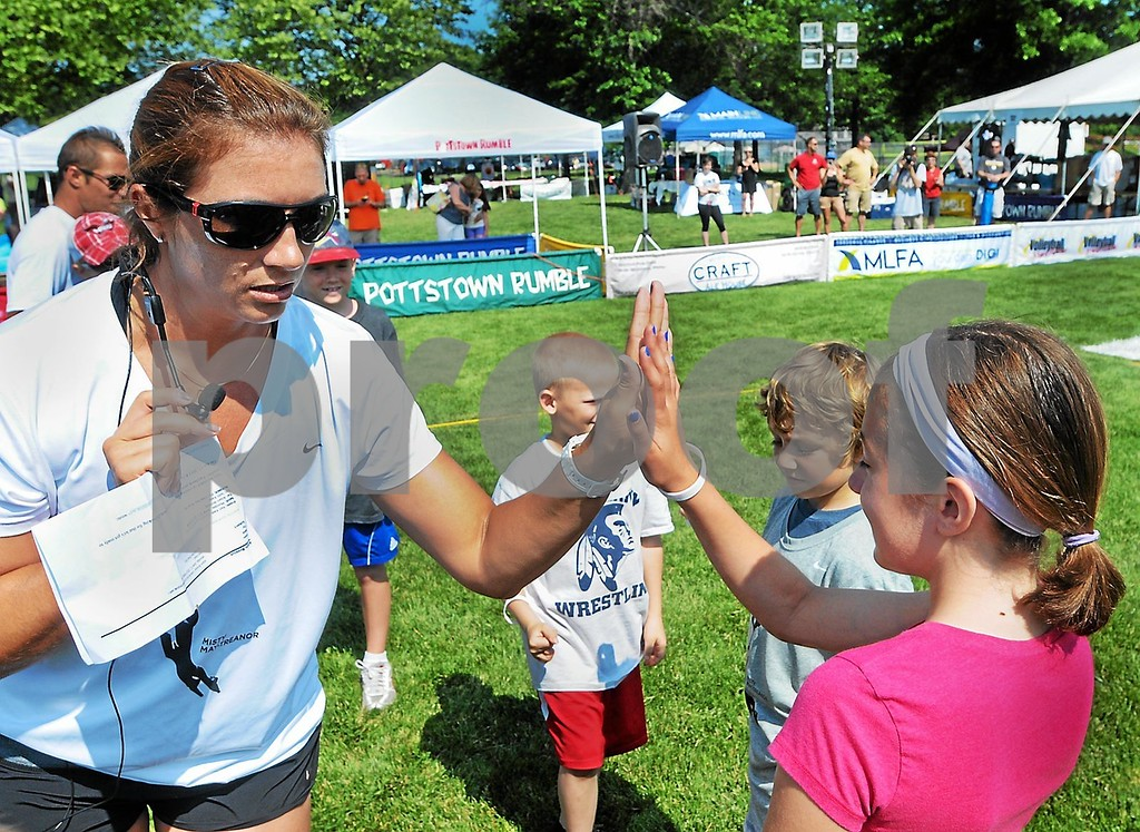 . Misty May-Treanor gives out high fives to kids during a volleyball clinic Thursday, June 20, 2013, at Memorial Park in Pottstown. (Photo by John Strickler/The Mercury)