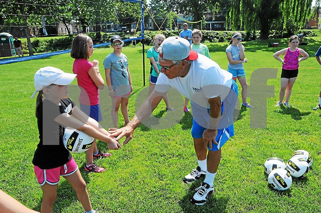 . Butch May helps instruction children on their arm form during the youth volleyball clinic at Pottstown\'s Memorial Park Thursday, June 20, 2013. (Photo by John Strickler/The Mercury)