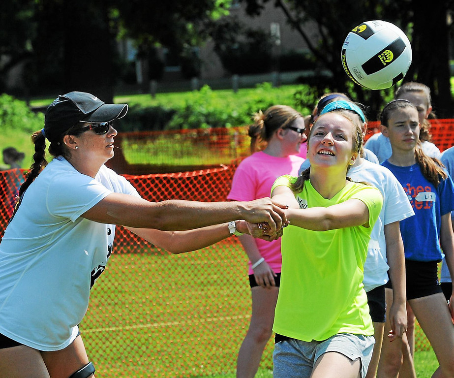 . Maddy Lewis gets volleyball instruction from Olympic gold medalist Misty May-Treanor during the youth clinic held Thursday in Pottstown\'s Memorial Park. (Photo by John Strickler/The Mercury)