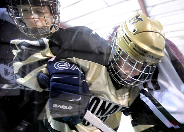 "Fairview High School's Noah Zimmerman, center, gets checked against the glass by Cheyenne Mountain's  Zach Werner, left,  during a hockey game against Cheyenne Mountain High School on Wednesday, Dec. 14, at Boulder Valley Ice at Superior in Superior. Monarch won the game 7-1. For more photos of the game go to  <a href=""http://www.dailycamera.com"">http://www.dailycamera.com</a><br /> Jeremy Papasso/ Camera"