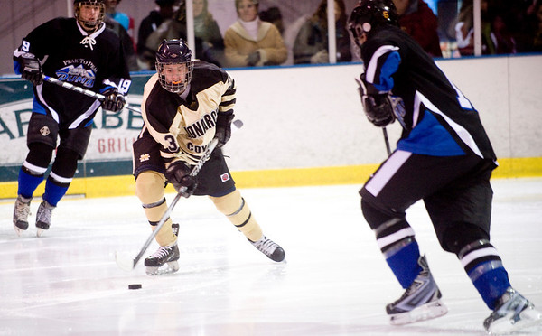 Monarch's Bennett Fauver (center) skates through Peak to Peak's Ryan Hartwig (left) and another defender during their game at Boulder Valley Ice in Superior, Friday, Jan. 8, 2009. <br /> KASIA BROUSSALIAN