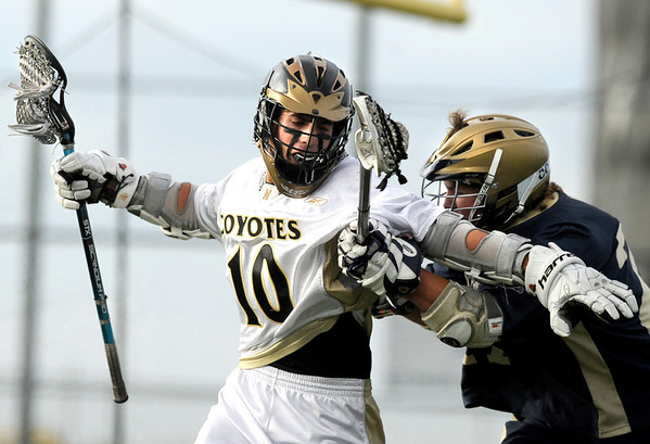 "Monarch High School's Nate Puldy tries to shake a defender while moving the ball upfield during a lacrosse game against Evergreen High School at Monarch on Friday, May, 6. Monarch won the game 11-5. For more photos go to  <a href=""http://www.dailycamera.com"">http://www.dailycamera.com</a><br /> Jeremy Papasso/ Camera"