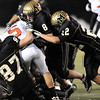 Monarch's Joe Kawulok (left), Tyler Slade (center right) and Ryan Muller (right) stop Loveland's Andrew Eberle (middle left) for a loss during their football game at Centaurus in Lafayette, Colorado November 20, 2009. CAMERA/Mark Leffingwell