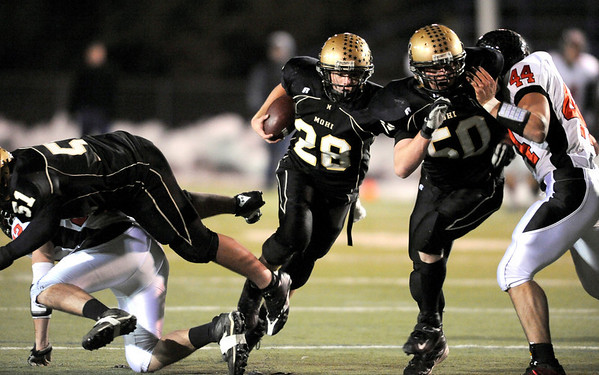 Monarch's Ryan Hamlin gets blocks from Greg Ancmon (left) and Brennan Ramos right for a first down against Loveland during their football game at Centaurus in Lafayette, Colorado November 20, 2009. CAMERA/Mark Leffingwell
