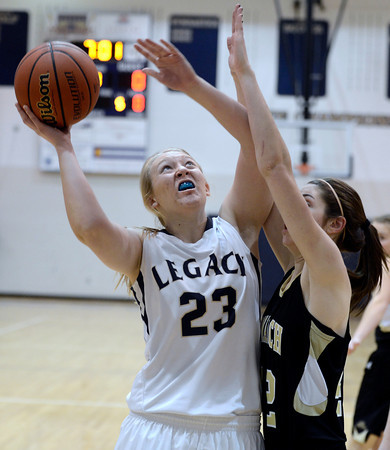 "Legacy High School's Caitlyn Smith takes a shot over Kelly O'Flannigan during a game against Monarch High School on Friday, Jan. 11, at Legacy High School in Broomfield. For more photos of the game go to  <a href=""http://www.dailycamera.com"">http://www.dailycamera.com</a><br /> Jeremy Papasso/ Camera"