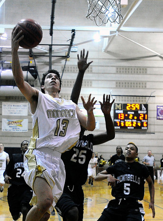"""Monarch High School's Nathan Brooks, left, goes for a layup past Montbello High School's Malik Hart, No. 25, on Friday, Dec. 2, during a game against Montbello High School at Monarch High School in Louisville. For more photos of the game go to  <a href=""""http://www.dailycamera.com"""">http://www.dailycamera.com</a><br /> Jeremy Papasso/ Camera"""