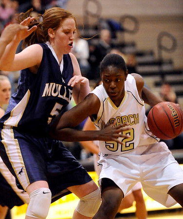 Monarch's Alexus Johnson (right) pushes off Mullen's Kirsten Hess (left) during their basketball game Monarch High School in Louisville, Colorado December 8, 2009.  CAMERA/Mark Leffingwell
