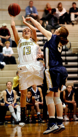 Monarch's Ashton Davis (left) takes a shot while under pressure from Mullen's Kirsten Hess (right) during their basketball game Monarch High School in Louisville, Colorado December 8, 2009.  CAMERA/Mark Leffingwell